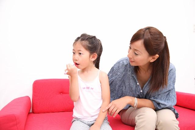 歯磨きする女の子と見守る母親