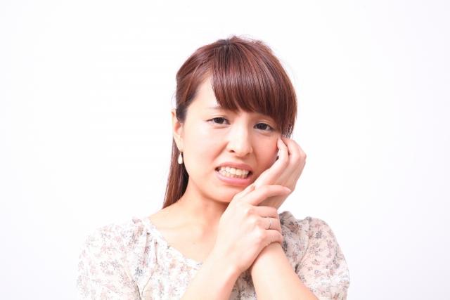 歯の痛みに堪える女性